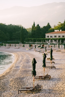 Деревянные шезлонги на песчаной платформе на закате вилла милочер в черногории недалеко от острова свети