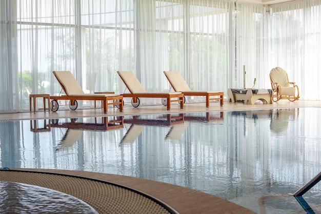 Деревянные шезлонги, плетеные кресла-качалки и массажная кровать у воды в закрытом бассейне