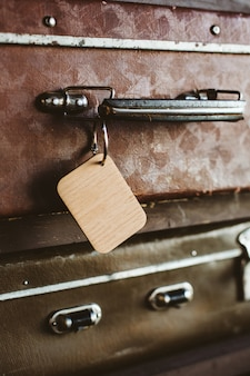 Wooden luggage tag on the handle of an old suitcase. close up.
