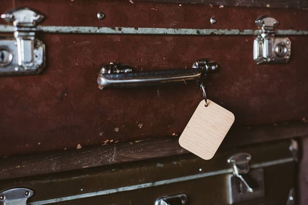 Wooden luggage tag on the handle of an old suitcase. mock up