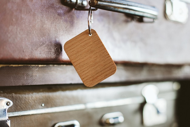 Wooden luggage tag on the handle of an old suitcase.