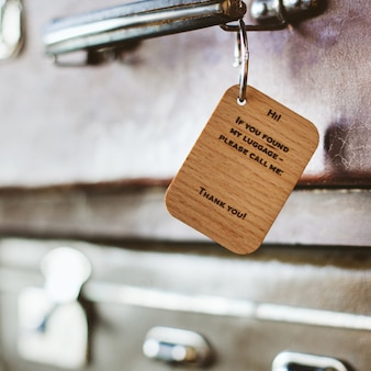 Wooden luggage tag with the inscription on the handle of a vintage suitcase.