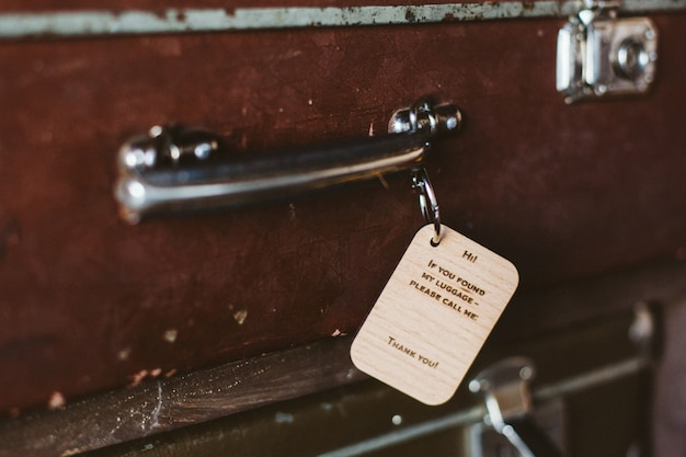 Wooden luggage tag with the inscription on the handle of a vintage suitcase