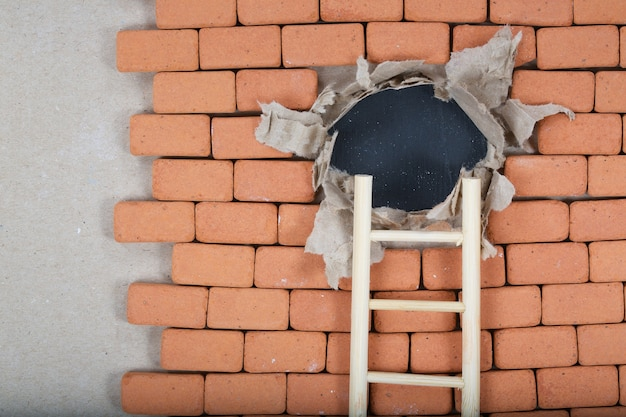 Wooden made ladder goes to the hole in the brick wall
