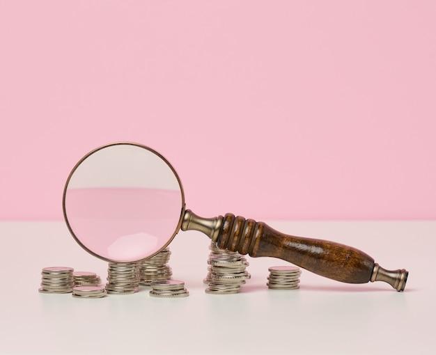 テーブルの上の木製の拡大鏡と白いコイン。所得成長の概念、投資の高い割合。新しい収入源、補助金を探す