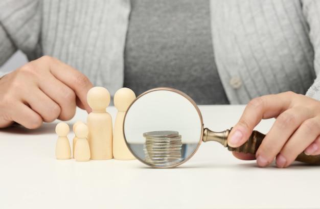 白いテーブルの上の木製の拡大鏡と白いコイン。所得成長の概念、投資の高い割合。新しい収入源、補助金を探す