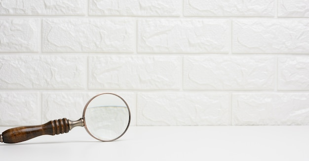 Wooden magnifier on a white background. the concept of uncertainty and the search for solutions, doubts, copy space