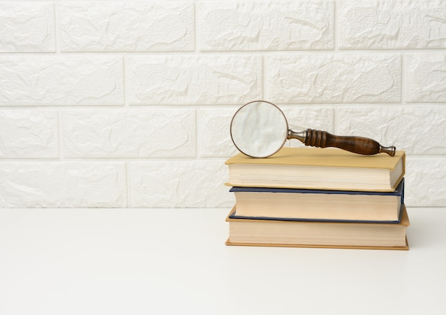 A wooden magnifying glass lies on a stack of books, new knowledge and discoveries are reading books