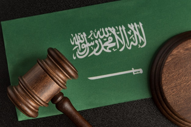 Wooden mallet justice on saudi arabia flag. law library. law and justice concept.