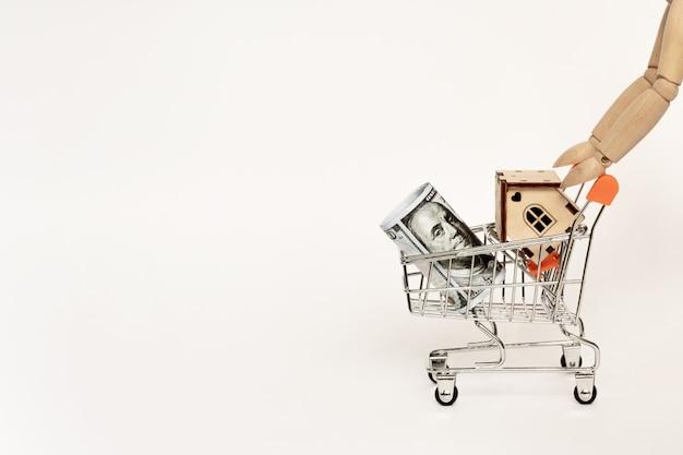 木製の男は、住宅投資のための木製のテーブルにお金のドル紙幣とミニショッピングカートで家モデルを運ぶ。