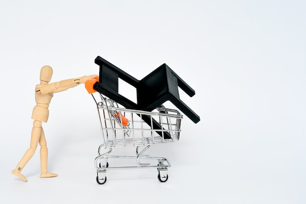Wooden man carry supermarket shopping whith black chair in it isolated on white background