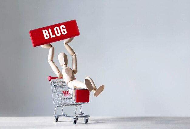 Деревянный человек держит красный деревянный блок со словом блог, концепция