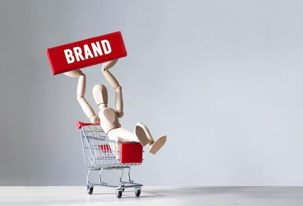 Деревянный человек держит красный деревянный блок со словом бренд, концепция Premium Фотографии
