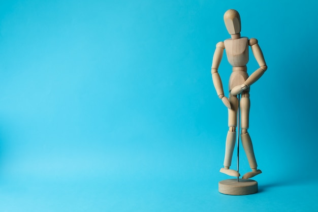 Wooden man hold his crotch on blue. urology