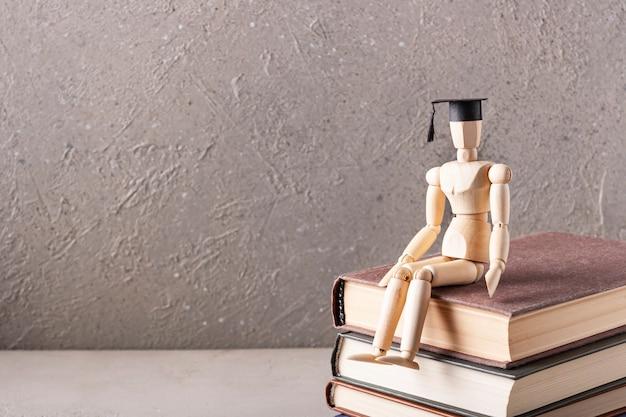 学生帽をかぶった木製の男が本に座っています