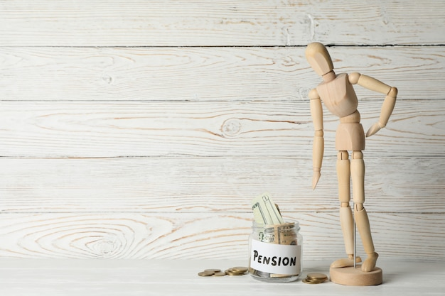 Wooden man and jar with money on wooden surface