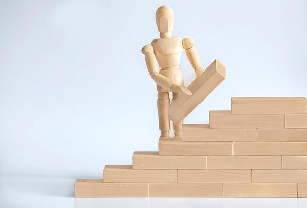 Рука деревянного человека штабелирования деревянных блоков. концепция бизнеса и развития.