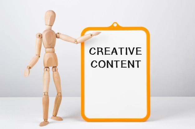 Деревянный человек показывает рукой на доску с текстом, креативное содержание, концепция