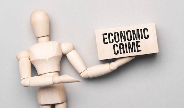 나무 남자는 텍스트 경제 범죄와 화이트 보드에 손으로 보여줍니다