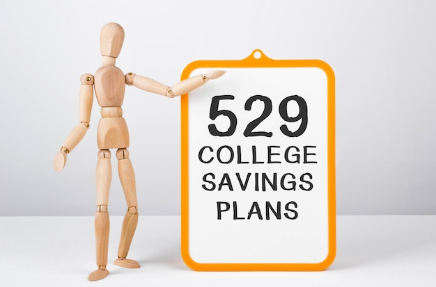 Wooden man shows with a hand to white board with text 529 college savings plans.