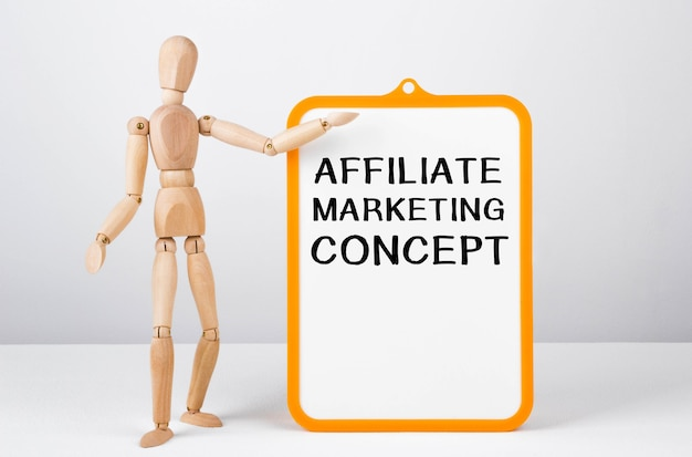 Wooden man shows with a hand to white board with text affiliate marketing concept.