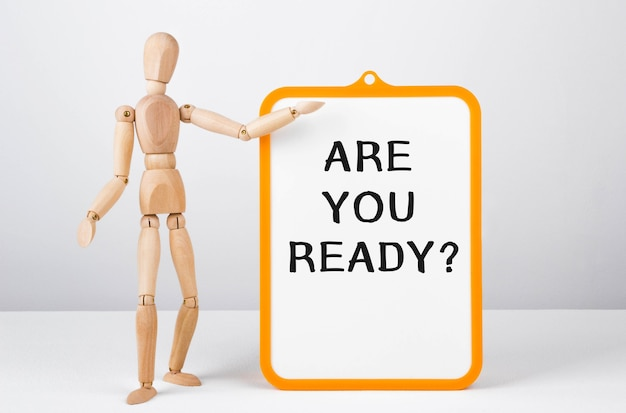 Wooden man shows with a hand to white board with text are you ready