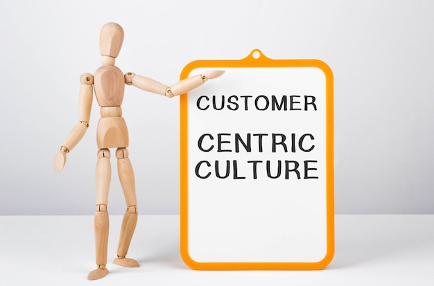 Wooden man shows with a hand to white board with text customer centric culture