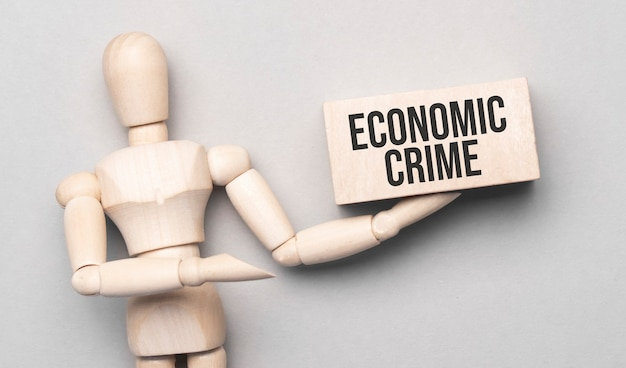 Wooden man shows with a hand to white board with text economic crime
