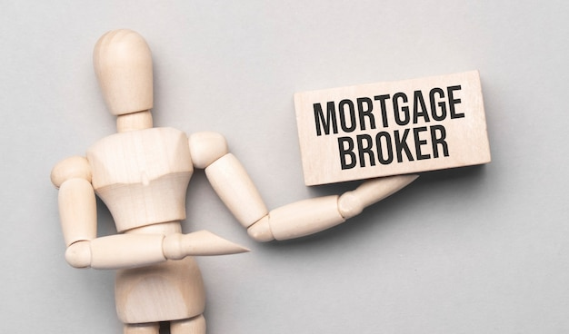 Wooden man shows with a hand to white board with text mortgage broker, concept