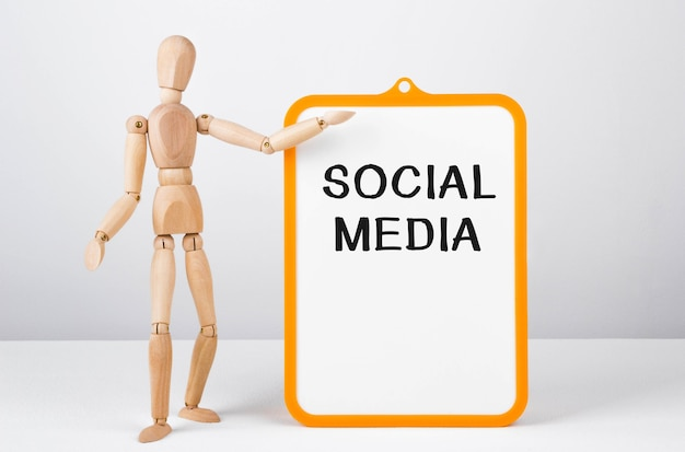 Wooden man shows with a hand to white board with text social media,concept