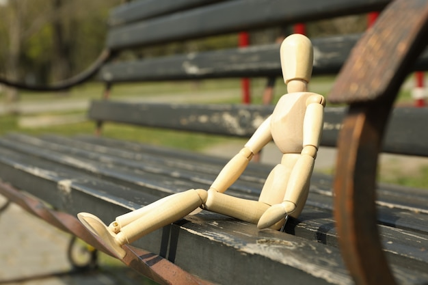 Wooden man sits on bench. spring day