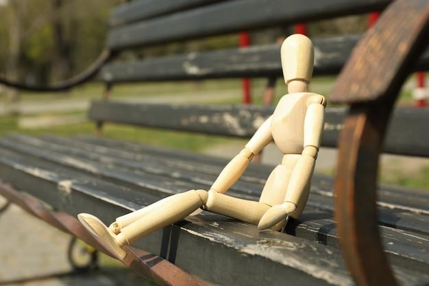 木製の男がベンチに座っています。春の日