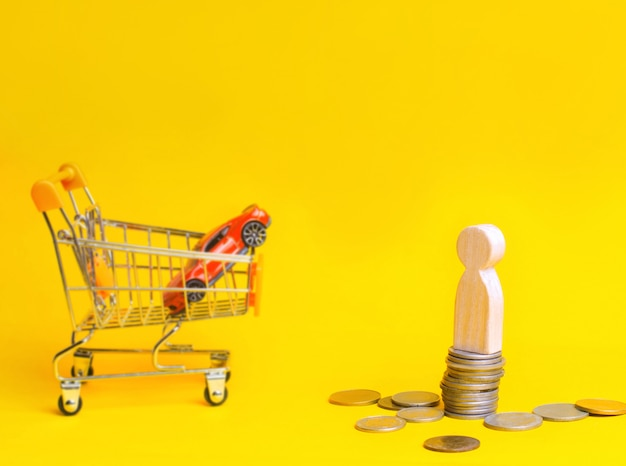 Wooden man stand on coins on the background of a car and a basket from a supermarket.