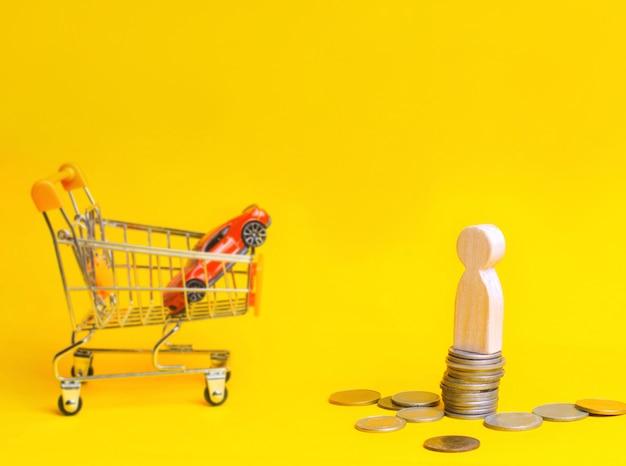 Деревянная стойка человека на монетках на предпосылке автомобиля и корзины от супермаркета.