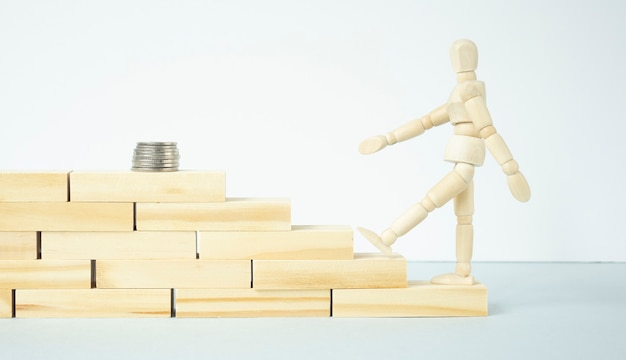 A wooden man walking up the steps to get to the coin stack on white background