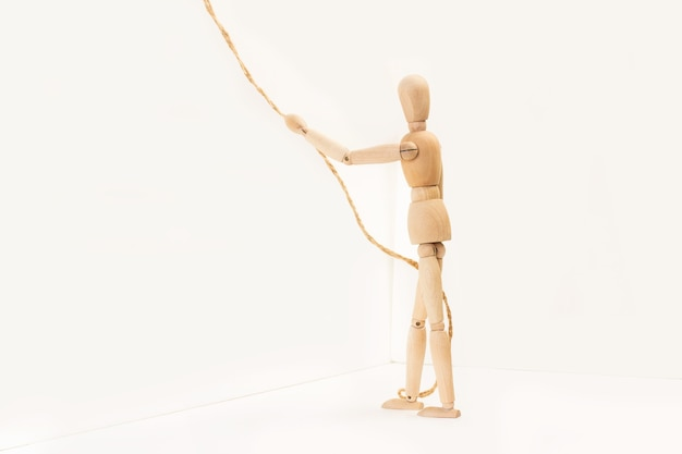 A wooden manequin toy holding holding a thin rope in his hand