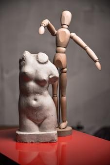 손과 머리가없는 나무 마네킹과 석고 여성의 몸