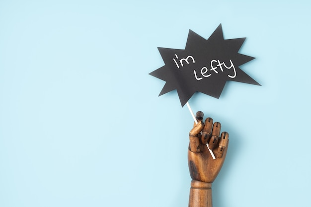 Wooden mannequin hand with sign i am lefty over blue background. international left handers day concept. copy space
