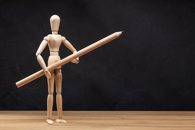 鉛筆を持つ木製のマネキン。黒板の背景。図面のコンセプト。コピースペース
