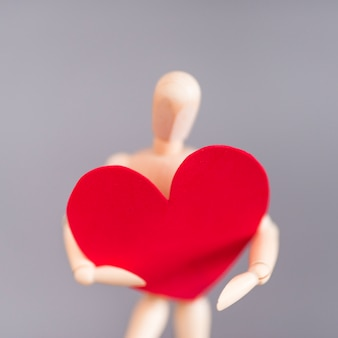 Wooden mannequin holding big red heart