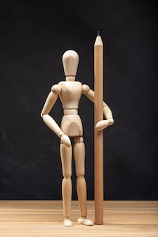 Wooden mannequin holding a pencil. drawing or design concept