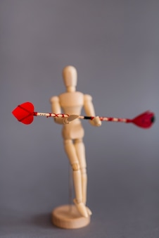 Wooden mannequin holding red love arrow