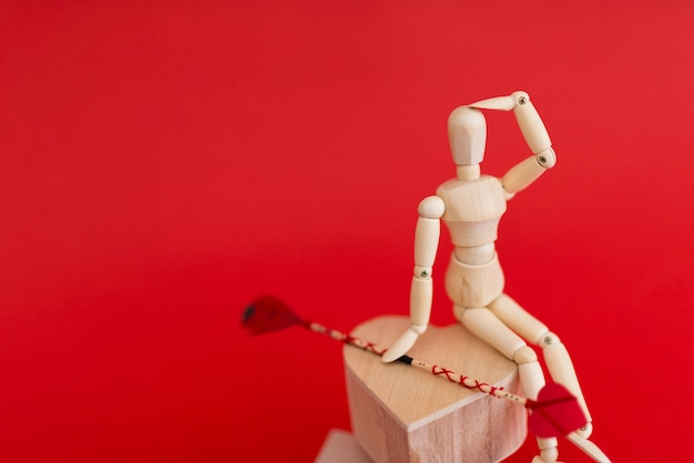 Wooden mannequin sitting on heart with love arrow
