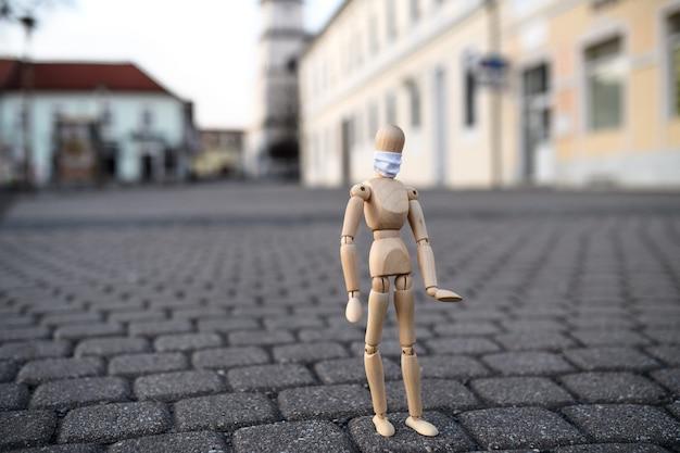 Деревянный манекен с маской для лица, гуляющий по городу, вирус короны и концепция изоляции.