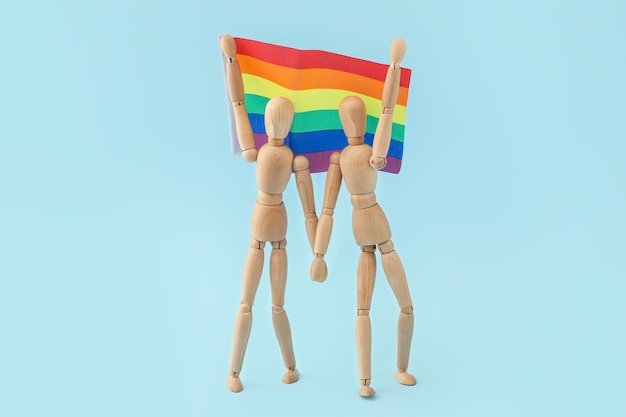 Wooden mannequins and rainbow flag on blue