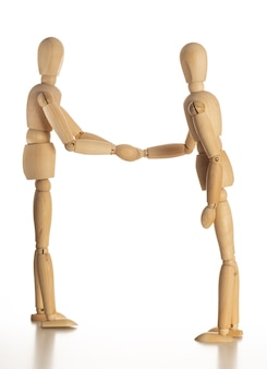 Wooden mannequins shaking hands with isolated on white background