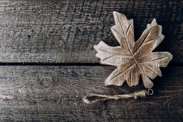 Wooden maple leaf on a wooden background. symbol of canada. top view, copy space