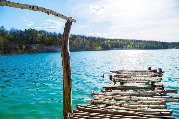 木製の石積みは、隔離された水の上に立っています。木製の橋から湖への入り口