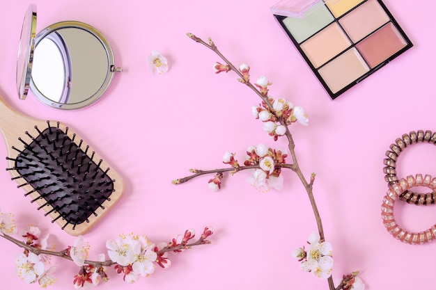나무 마사지 빗, 머리카락 용 나선, 작은 둥근 거울, 컨실러 팔레트 및 분홍색 배경에 꽃 살구 가지. 여성의 아름다움의 개념. 집에서 헤어 및 바디 케어.