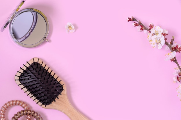 Wooden massage comb, spirals for hair, small round mirror and flowering apricot branchs on pink background. concept of female beauty. hair care at home. copy space
